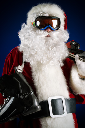 ski mask: Santa Claus is standing in the ski mask and holding a skiing. Over dark . Christmas. Stock Photo