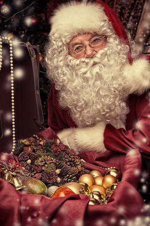 Santa Claus at home preparing for Christmas gifts. photo