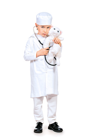 Full length portrait of a little boy playing a doctor veterinarian. Different occupations. Isolated over white. photo