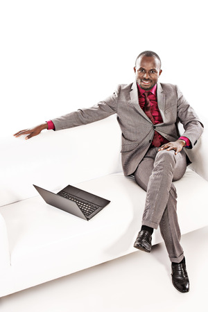 Confident african american business man working on his laptop on a sofa. Isolated over white. photo