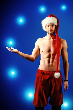 Portrait of a handsome sexual young man in Christmas hat.  photo