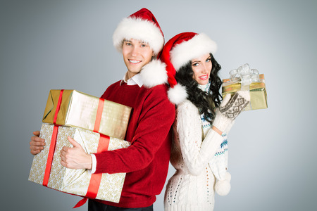 Cheerful young couple in warm winter clothing and Christmas caps holding presents.  photo