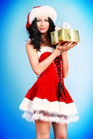 Portrait of a charming smiling young woman in Christmas costume with gift. photo