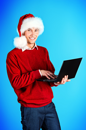 clause: Young businessman with Santa Hat and laptop Stock Photo