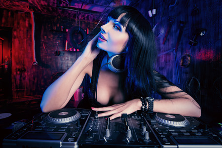 Beautiful sexual DJ girl working on a party in the old garage. photo