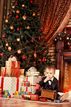Little boy playing with toys at home near the fireplace and Christmas tree. Stock Photo - 23805537