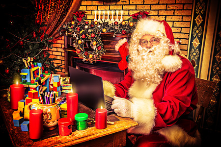 Modern Santa Claus sitting with a laptop at his home. Christmas. photo