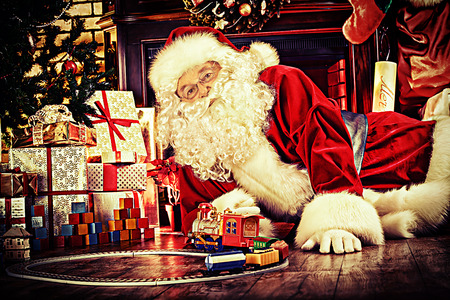 Santa Claus playing with toys under the Christmas tree. photo