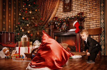 Little boy playing with toys at home near the fireplace and Christmas tree. Stock Photo - 23827700
