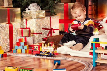 Little boy playing with toys at home near the fireplace and Christmas tree. Stock Photo - 23827731