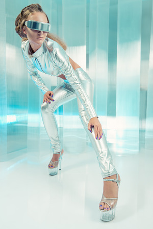 Beautiful young woman in silver latex costume with futuristic hairstyle and make-up. Sci-fi style. photo