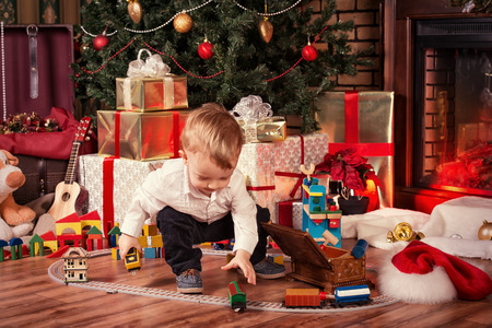 Little boy playing with toys at home near the fireplace and Christmas tree.