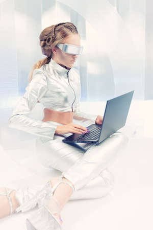Beautiful young woman in silver latex costume with futuristic hairstyle and make-up working on a laptop  Sci-fi style  photo