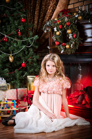 Cute little girl sitting on a floor near the fireplace and Christmas tree. Stock Photo - 23831709