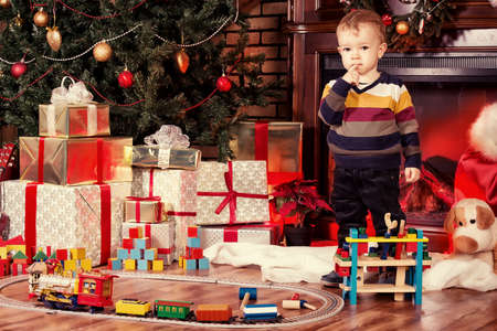 christmas toys: Little boy playing with toys at home near the fireplace and Christmas tree.