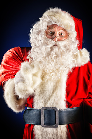 Portrait of a traditional Santa Claus with Christmas gifts. Over dark background.  photo