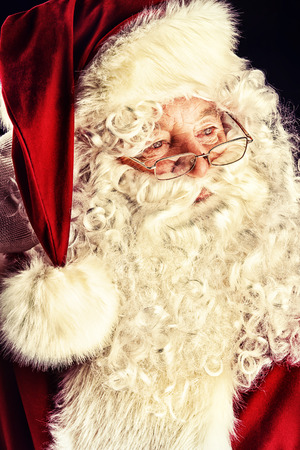 Portrait of a traditional Santa Claus. Over dark background. Christmas. photo