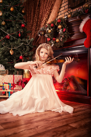 Beautiful little girl sitting on a floor near the fireplace and Christmas tree and playing the violin. photo