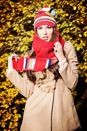 Portrait of pretty young woman in a warm coat and knitted hat at the autumn park. photo