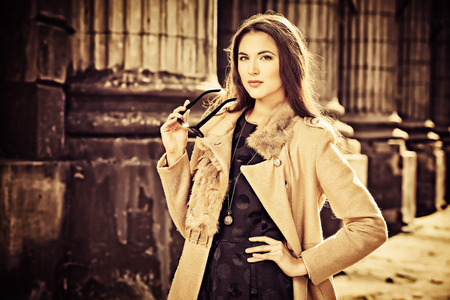 Beautiful fashionable woman standing on the city street. Sepia. photo