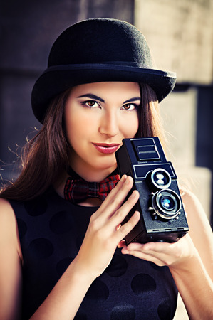 Beautiful brunette standing on a city street and holding the old camera. Retro style. photo