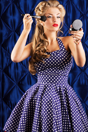 Portrait of a charming pin-up girl doing makeup in front of a mirror. photo