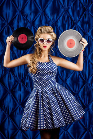 Pretty pin-up woman with retro hairstyle and make-up posing with vinyl record over vintage background. photo