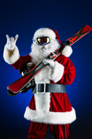 Santa Claus is standing in the ski mask and holding a skiing. Christmas.  photo