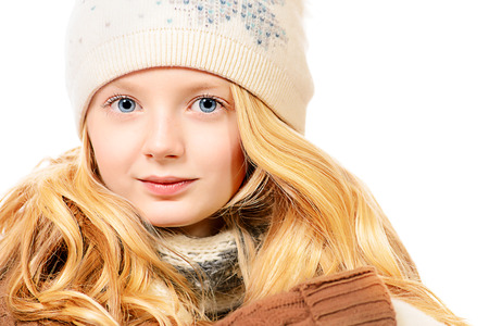 Portrait of a pretty ten years girl in warm clothes smiling at camera. Isolated over white. photo