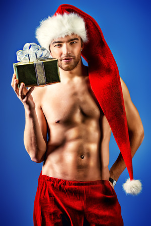 Sexual young man in Christmas costume holding a gift.  photo