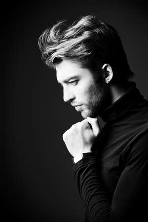 imposing: Imposing man in elegant black clothes posing over dark background. Profile portrait.