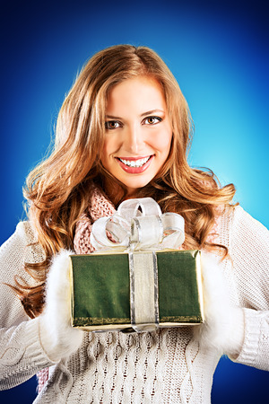 Beautiful smiling young woman in warm clothes holds a gift.  photo