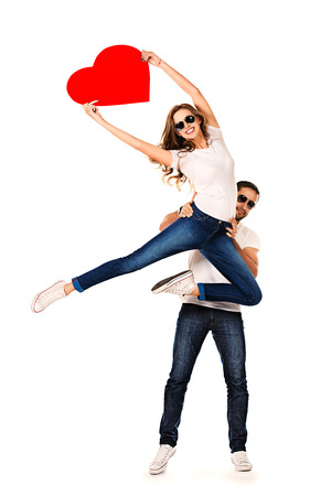 Happy young people in love posing with big red heart. Isolated over white. photo
