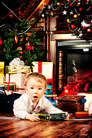 Little boy playing with toys at home near the fireplace and Christmas tree. Stock Photo - 23979005
