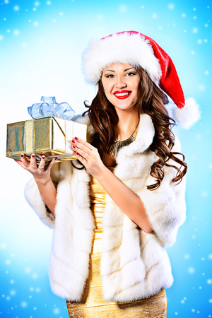 Beautiful smiling young woman in evening dress holding a gift. Christmas. photo