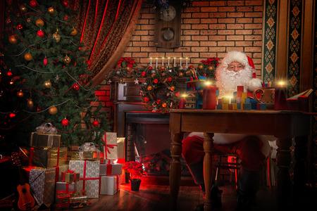 Santa Claus making Christmas gifts at home. photo