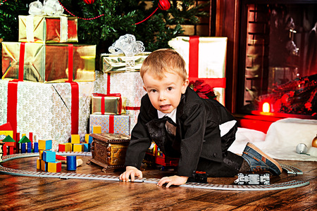 Little boy playing with toys at home near the fireplace and Christmas tree. Stock Photo - 23979070