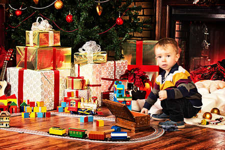 Little boy playing with toys at home near the fireplace and Christmas tree. Stock Photo - 23979071