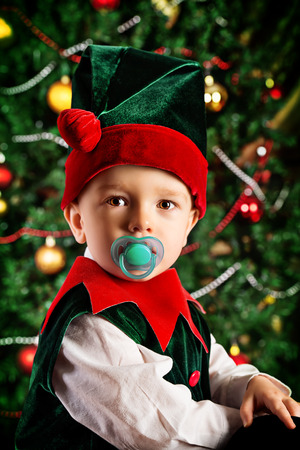 Portrait of a little boy dressed as an elf at home near the Christmas tree. Stock Photo - 23979076