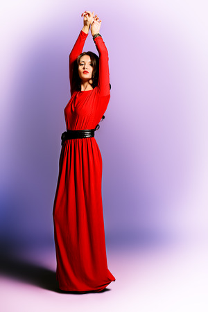 Fashion shot of a gorgeous young woman in elegant red dress. photo