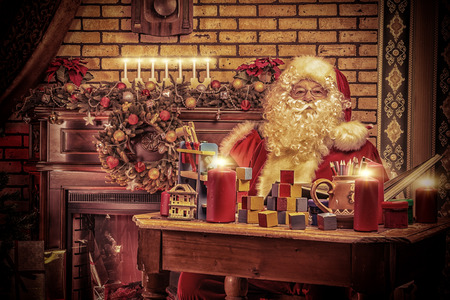 Santa Claus making Christmas gifts at home. photo