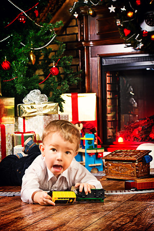 Little boy playing with toys at home near the fireplace and Christmas tree. Stock Photo - 23979131