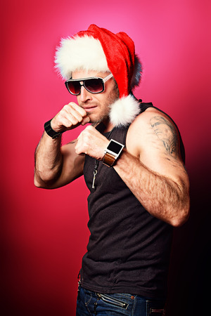 tempter: Portrait of a handsome brutal man in Christmas hat. Over red wall.