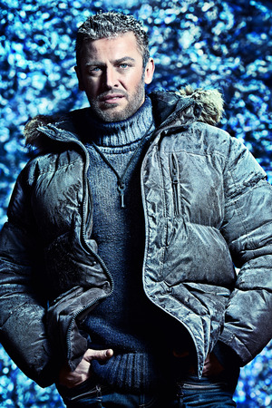 Portrait of a handsome brutal man dressed in winter clothes, covered with frost. photo