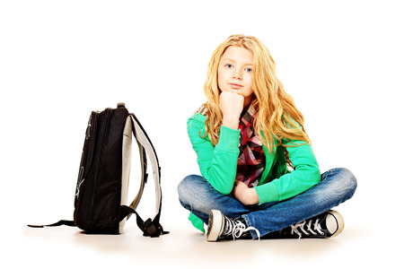 schoolbag: Cute ten years girl sitting on the floor next to her school backpack. Isolated over white. Stock Photo