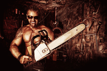 Expressive handsome muscular man with a chainsaw in the old garage. photo
