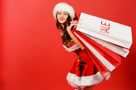 Attractive young woman in Santa Claus costume holds shopping bags over red background. Christmas. photo