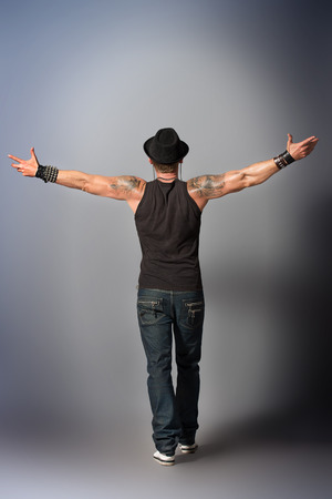 outstretched arms: A man stands with his back, arms outstretched to the side of happiness.