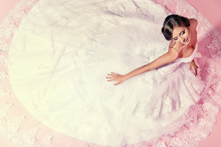 top model: Beautiful charming bride in a luxurious dress looking up. Over pink background.