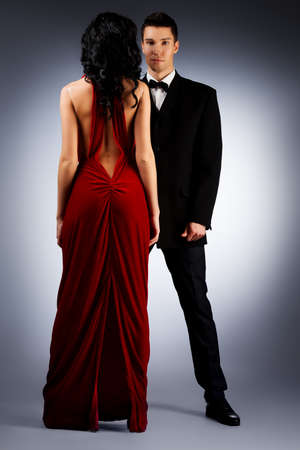 girl in red dress: Beautiful young couple in love in evening dresses posing at studio. Stock Photo